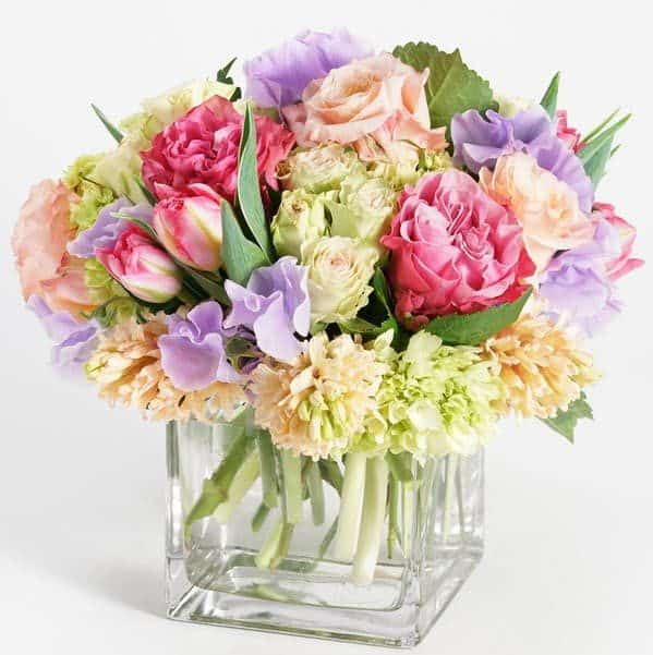 Enjoy the natural beauty of Earth's reawakening and indulge your senses with this refreshing collection of pristine Spring blooms. Arranged in a glass cube vase, fragrant hyacinth are nestled amidst clusters of pink tulips, peach roses and mini green hydrangea and accented with delicate waves of lavender sweet pea.
